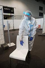 Deutschland  Bremen - Medizinische Fachangestellte Corona-Testzentrum in einer Messehalle desinfiziert Stuhl