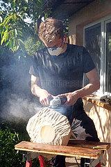 Berlin  Deutschland  Teenager bearbeitet ein Stueck Holz mit einer Fraese