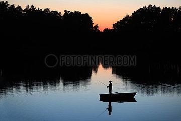 Dranse  Deutschland  Silhouette: Jugendlicher in einem Boot angelt bei Daemmerung in einem See