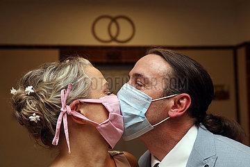 Berlin  Deutschland  Brautpaar kuesst sich in Zeiten der Coronapandemie mit Mund-Nasen-Schutz