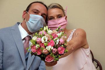 Berlin  Deutschland  Brautpaar zeigt in Zeiten der Coronapandemie stolz den Brautstrauss