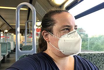 Berlin  Deutschland  Frau in einer S-Bahn traegt in Zeiten der Coronapandemie eine Atemmaske