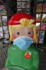 Berlin  Deutschland  Pixiefigur mit Mund-Nasen-Schutz vor einem Schreibwarenladen