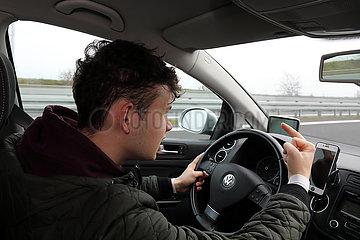 Gruenheide  Deutschland  junger Mann zeigt beim Autofahren den Mittelfinger
