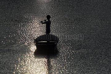 Dranse  Deutschland  Silhouette: Jugendlicher in einem Boot angelt am Abend in einem See