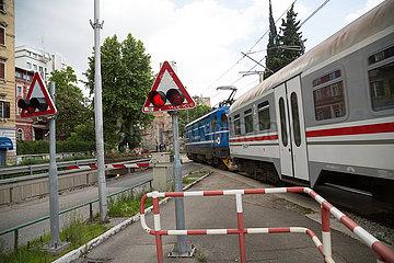 Kroatien  Rijeka - Personenzug passiert Bahnuebergang in der Stadt - Hrvatske zeljeznice (HZ): Kroatische Bahnen  die staatliche kroatische Bahngesellschaft