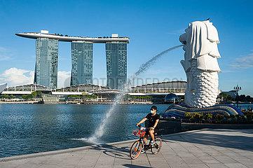 Singapur  Republik Singapur  Ein Radfahrer mit Mundschutz faehrt durch den Merlion Park in Marina Bay