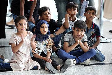 Dubai  Vereinigte Arabische Emirate  Kinder sitzen erwartungsvoll auf dem Boden