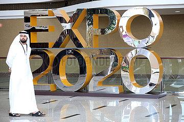 Dubai  Vereinigte Arabische Emirate  Mann in Landestracht laeuft an einem Werbeaufsteller fuer die Expo 2020 vorbei