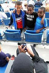 Dubai  Vereinigte Arabische Emirate  Einheimische Frau fotografiert drei kleine Jungen mit ihrem Smartphone