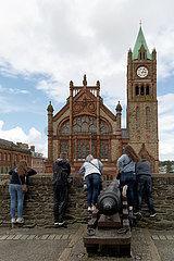 Grossbritannien  Derry - Junge Leute beugen sich ueber die Ballustrade der Derry Walls Richtung dem neogotischen Rathaus The Guildhall
