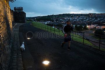 Grossbritannien  Derry - Katholischer Stadtteil Bogside  der eine besondere Rolle im Nordirlankonflikt spielt  Mann mit Hund bei den Derry Walls