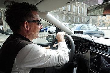 Berlin  Deutschland  Mann faehrt in der Stadt entspannt Auto