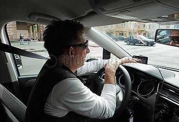 Berlin  Deutschland  Autofahrer tippt auf seinem Navigationsgeraet das Fahrziel ein