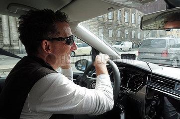 Berlin  Deutschland  Mann telefoniert waehrend der Autofahrt ohne Freisprechanlage mit dem Mobiltelefon