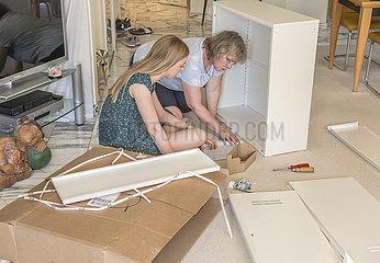 zwei Frauen bauen gemeinsam Ikea-Schrank auf
