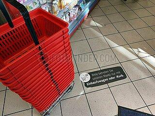 Einkaufskoerbe mit Corona-Hinweis in Supermarkt