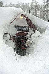 Krippenbrunn  Oesterreich  Junge befreit den Eingang einer Skihuette von den Schneemassen