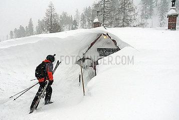 Krippenbrunn  Oesterreich  Skifahrer erreicht seine von Schneemassen bedeckte Skihuette