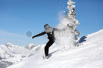 Schruns  Oesterreich  Teenager faehrt Snowboard abseits der Piste im Tiefschnee