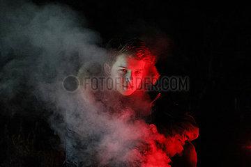 Berlin  Deutschland  Teenager schaut mit coolem Blick durch eine Rauchschwade