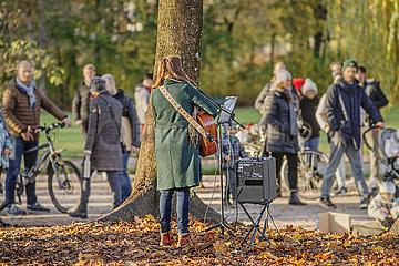 Strassenmusikerin im Englischen Garten  Muenchen  November 2020