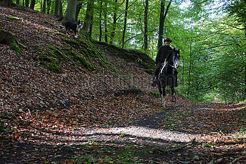 Neu Kaetwin  Mann reitet in Begleitung seines Hundes durch einen Wald