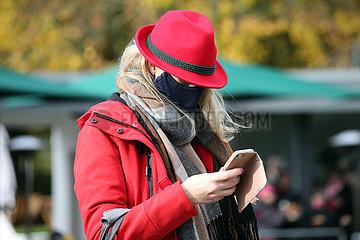 Hannover  Deutschland  Frau mit Hut und Mund-Nasen-Schutz schaut auf ihr Smartphone