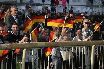 Hoppegarten  Deutschland  Menschen schwenken am Tag der Deutschen Einheit Nationalfahnen. Sven Siebert  Oberbuergermeister der Gemeinde Hoppegarten (links) schaut zu