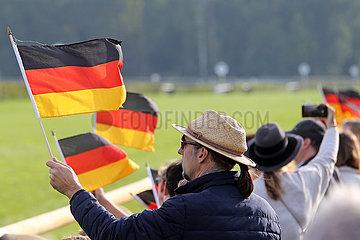 Hoppegarten  Deutschland  Mann haelt am Tag der Deutschen Einheit die Nationalfahne hoch