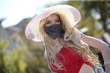 Iffezheim  Deutschland  Fashion: Elegant gekleidete Frau mit Hut traegt Mund-Nasen-Schutz