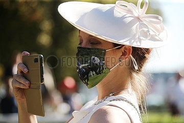Iffezheim  Deutschland  Fashion: Elegant gekleidete Frau mit Hut traegt einen DIY-Mund-Nasen-Schutz und fotografiert mit ihrem Smartphone