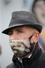 Hannover  Deutschland  Mann mit Hut traegt einen Mund-Nasen-Schutz mit Rauchermotiv