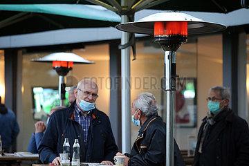 Hannover  Deutschland  Menschen stehen in Zeiten der Coronapandemie im Freien unter eingeschalteten Heizpilzen
