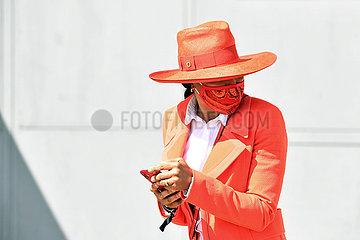 Hamburg  Deutschland  Fashion: Elegant gekleidete Frau mit Hut traegt Mund-Nasen-Schutz und schaut sich um