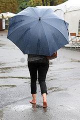 Dresden  Deutschland  Frau laeuft bei Schlechtwetter barfuss allein unter ihrem Regenschirm