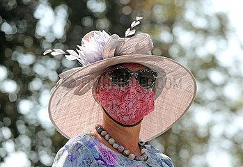 Iffezheim  Deutschland  Fashion: Elegant gekleidete Frau mit Hut und Sonnenbrille traegt Mund-Nasen-Schutz