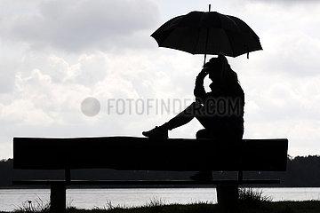 Dranse  Deutschland  Silhouette: Frau sitzt unter einem Regenschirm an einem See auf einer Bank