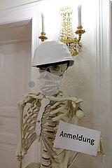 Berlin  Deutschland  Skelett in einer Arztpraxis traegt Bauhelm und Mund-Nasen-Schutz