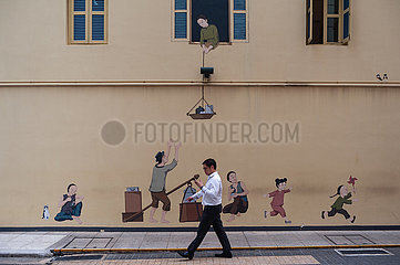 Singapur  Republik Singapur  Ein Bueroangestellter geht in Chinatown an einem Wandbild vorbei