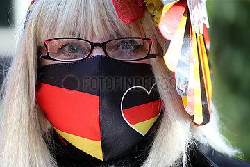 Hoppegarten  Deutschland  Frau traegt einen selbstgenaehten Mund-Nasen-Schutz in den deutschen Nationalfarben