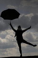 Dranse  Deutschland  Silhouette: Frau balanciert mit einem Regenschirm auf der Lehne einer Bank
