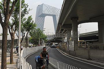 Peking  China  Alltagsszene mit Radfahrer im Zentrum der chinesischen Hauptstadt mit CCTV Headquarters