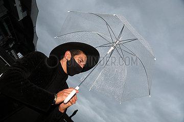 Hannover  Deutschland  Mann mit Hut und Regenschirm traegt einen Mund-Nasen-Schutz