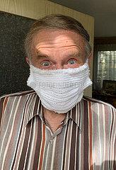 Neuenhagen  Deutschland  Senior traegt einen gehaekelten Mund-Nasen-Schutz