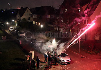 Berlin  Deutschland  Menschen schiessen auf der Strasse Roemische Lichter in den Himmel