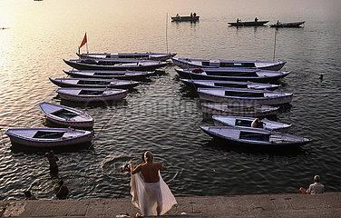 Varanasi  Indien  Menschen baden im heiligen Ganges mit Ruderbooten im Hintergrund