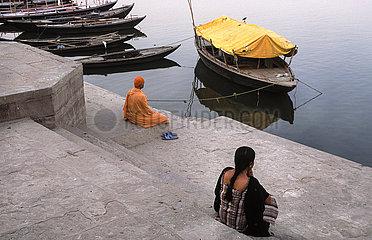 Varanasi  Indien  Menschen sitzen an einem Ghat entlang des heiligen Ganges