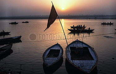 Varanasi  Indien  Morgenstimmung mit Ruderbooten am Ufer des Ganges waehrend Sonnenaufgang