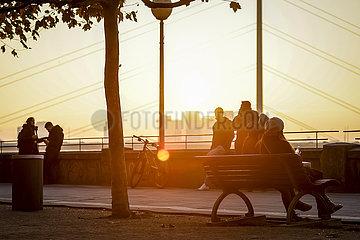 Jugendliche treffen sich in Zeiten der Coronapandemie zur Vorweihnachtszeit auf der Rheinpromenade  Duesseldorf  Nordrhein-Westfalen  Deutschland